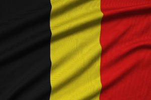 Belgium flag is depicted on a sports cloth fabric with many folds. Sport team waving banner