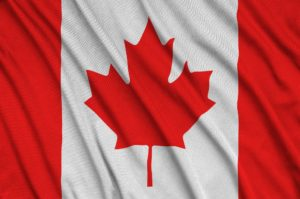 Canada flag is depicted on a sports cloth fabric with many folds. Sport team waving banner