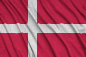 Denmark flag is depicted on a sports cloth fabric with many folds. Sport team waving banner