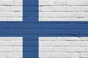 Finland flag depicted in paint colors on old brick wall close up