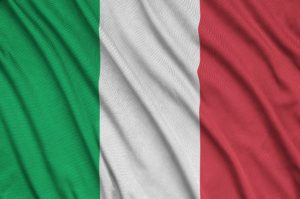 Italy flag is depicted on a sports cloth fabric with many folds. Sport team waving banner