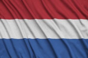 Netherlands flag is depicted on a sports cloth fabric with many folds. Sport team waving banner