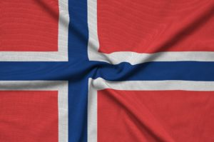 Norway flag is depicted on a sports cloth fabric with many folds. Sport team waving banner