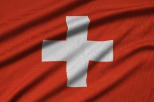 Switzerland flag is depicted on a sports cloth fabric with many folds. Sport team waving banner